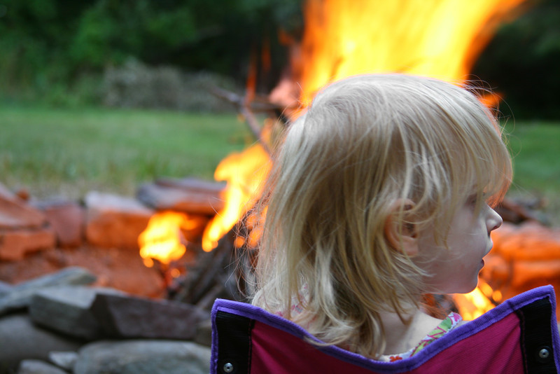 A little girl sits in a lawn chair while a fire rages just beyond her.