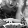 A little girl investigates a huge mushroom.