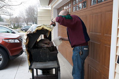 Mike adds water to the special double pan system inside the grill that makes the turkey moist and delicious.