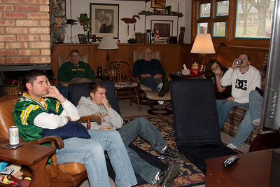 People gather in the family room to watch the Packers on the huge TV.