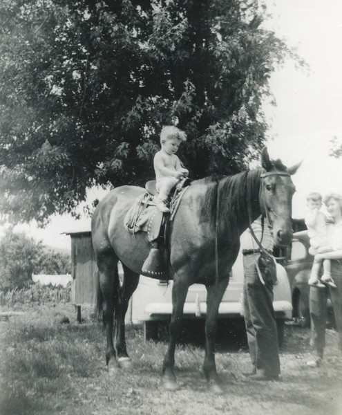 Dennis Colvin on horseback. My mom holding me to the far right.