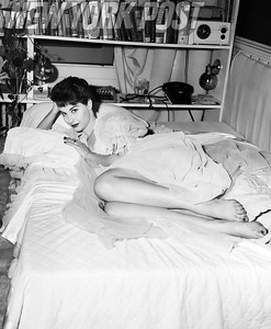 Gorgeous Nancy Berg poses beautifully laying in her bed. 1955