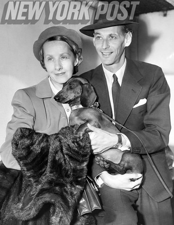 General manager of the Metropolitan Opera Association, Rudolph Bing and Mrs. Bing with their Daschund pup as they arrive to NYC on the Mauretania. 1950