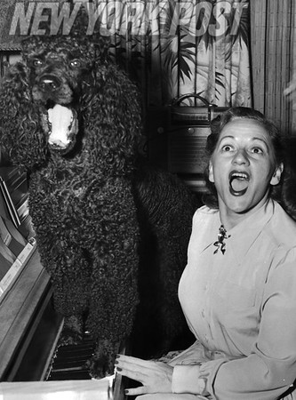 Singer Connee Boswell and her poodle hit a high note. 1955