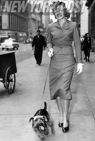 Miss America, Jean Bartel, walking her dog down a New York City street. 1943