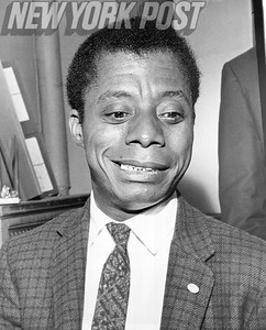 Writer James Baldwin is tickled during his interview with the New York Post. 1963