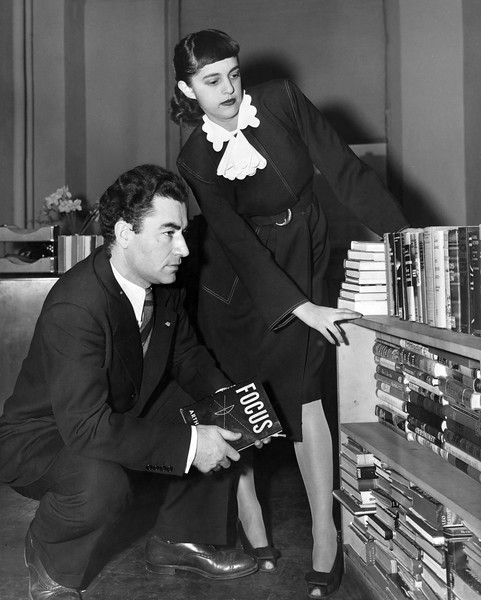 George and Marsha Braziller peruse their book shelves. 1940