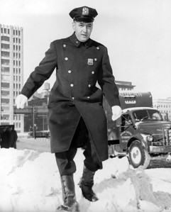 Patrolman John Cassese leaves the Beach St. Station on way to his new beat at 11th Av. And 18th St. December 11, 1960.