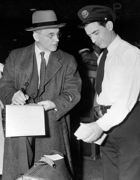 Dr. Isaiah Bowman president of John Hopkins University talking to customs inspector Max Leichman. 1948