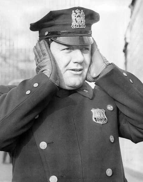 NYC Policeman tries to keep his ears warm in the frigid cold.