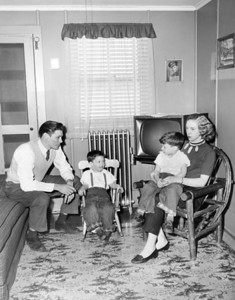 Donald and Shirley Culjak with their children Ronald and Donald in the living room of their stake boat. 1957