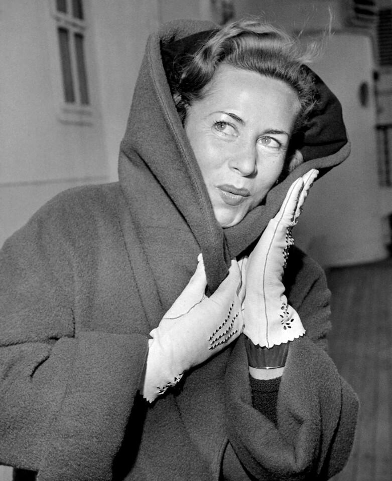Ice skater Helga Brandt, keeps warm as she arrives on the SS Liberte. 1958