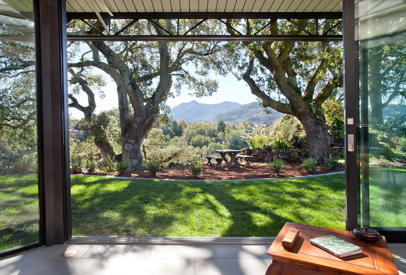 This site was made to order, framed by ancient oaks. Whats outside and whats inside?  Many ways to configure the space and the glass walls, allowing the mountains to come right inside the home.
