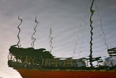 "Ghost Ship: This series was shot at the marina in Ventura, CA, about an hour before sunset. Instead of shooting the boats, masts and buildings directly, which I'd done many times, I pointed my camera at the water and shot just the reflections. The distortions are all caused by ripples in the water. During processing in Photoshop, I flipped the photographs vertically and tweaked them a bit, to get a more ""painterly"" look."