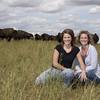 Bison ranchers in pasture with herd.