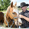 Rancher changes halters on his horse