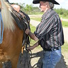 Rancher adjusts the saddle on his horse