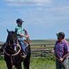 Boy pulls back lariat on horseback