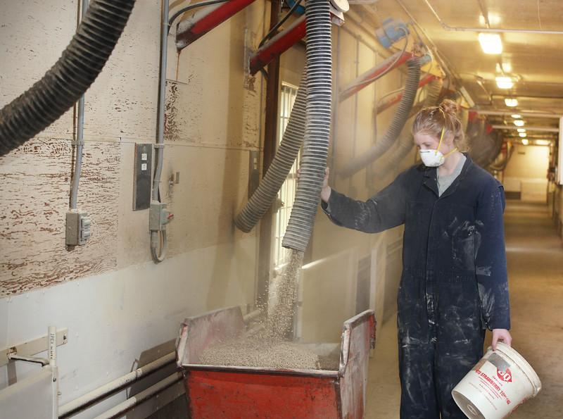 A technician fills a feed cart.