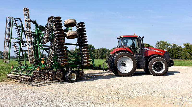 Bryce Buzzard moves one of his grandfather's farm implements. Buzzard wants to return to his family farm after he finishes his education. Charles Mills photo