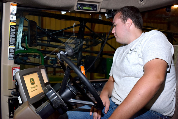 Ethan Matson loads a program on a tractor's GPS system on his parent's farm. Matson plans to return to work at the family farm after he graduates from college. Charles Mills photo