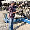 Bryce Buzzard makes adjustments to a planter on his grandfather's farm. Buzzard hopes to return to his family farm after graduating from college. Charles Mills photo