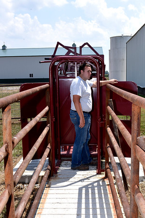 Ethan Matson checks a door on a corral project he completed with his father Keith and another Matson Farms, Inc. employee for Ethan's cows. Ethan owns 15 cows and one bull. Charles Mills photo