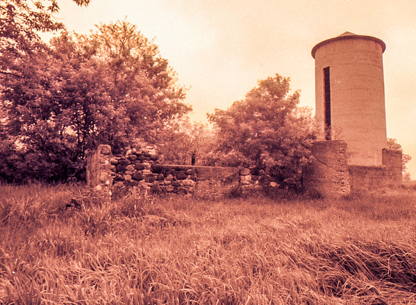 Foundation ruins and standing silo on dairy farm rural Wisconsin.