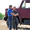 farmers talk beside grain truck