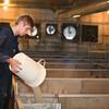 A technician manually fills the feeder