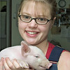 A technician holds a piglet. Piglets are usually weaned at 4 weeks of age.
