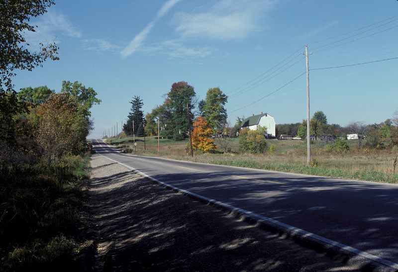 This is a view looking South along Haggerty Road showing farm buildings located 3/8 mile South of 13 Mile Road in Novi Township. There used to be a number of beautiful old barns on the West side of Haggerty Road in this area.