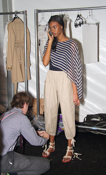 the designer makes last minute adjustments before the show.