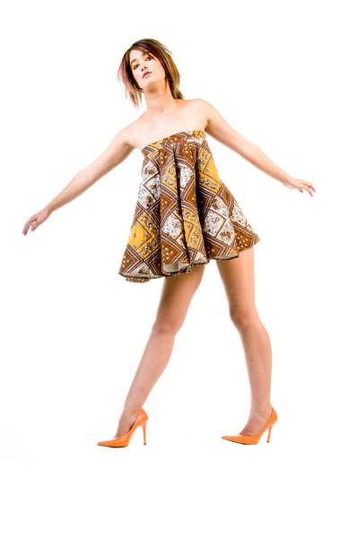 Beautiful young fashion model in a couture mini dress, large owl eye glasses and orange high heel shoes