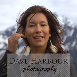 Beautiful Alaska Native woman, windblown, black leather, fur earrings, mountain, snow