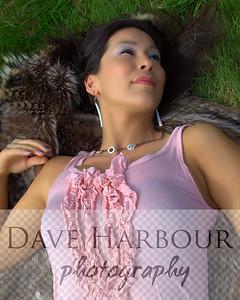 Beautiful Alaska Native woman, pensive, laying on wolf parka on grass, lake hood, Alaska Native jewelry