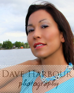 Beautiful Alaska Native woman, turquoise blouse and necklace, lakeside, summer.  Vertical: excellent for magazine cover.