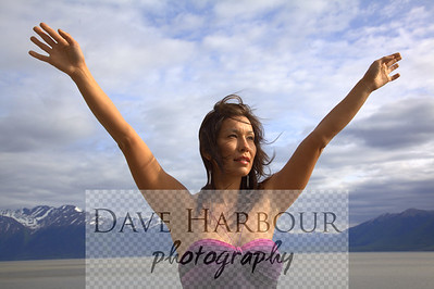 Beautiful Alaska Native woman, arms streached, sky and mountain and ocean background, Turnagain Arm, Alaska