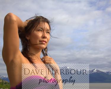 Beautiful Alaska Native woman, pensive, sky and mountain and ocean background, Turnagain Arm, Alaska