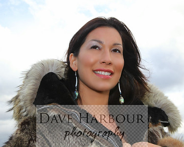 Beautiful Alaska Native woman, wolf parka, sky