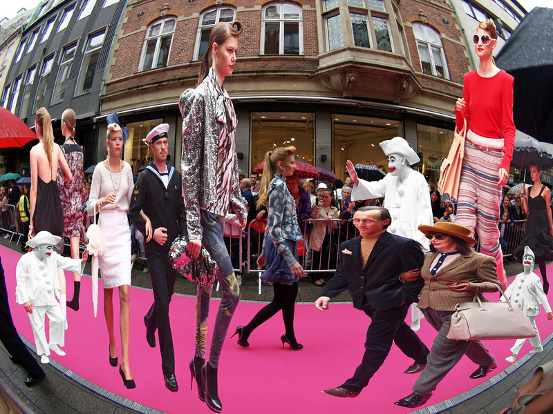 Fashion Pantomime.<br /> During the 2010 Copenhagen Fashion Trade Show, a catwalk was laid out in the walking street. 200 models would walk the mile to present the latest hot stuff. As an extra treat, they had invited some mariners to escort a few models - kind of cute. And they invited the Tivoli Pantomime figure Pjerrot: thus they unintendedly made an intelligent comparison of fashion shows to pantomime theater: both follow a rigid scheme with fixed, mute figures.<br /> Background photo was made with a semi fisheye lens, the figures were cut out of various photos and layered in Photoshop.<br /> Thanks to the fashion industry for a great photo opportunity - look forward to the next show.