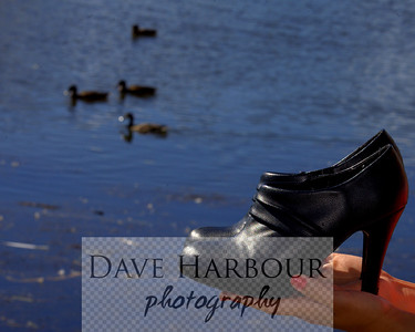 Black high heeled shoes held in woman's hands with ducks and pond in background.