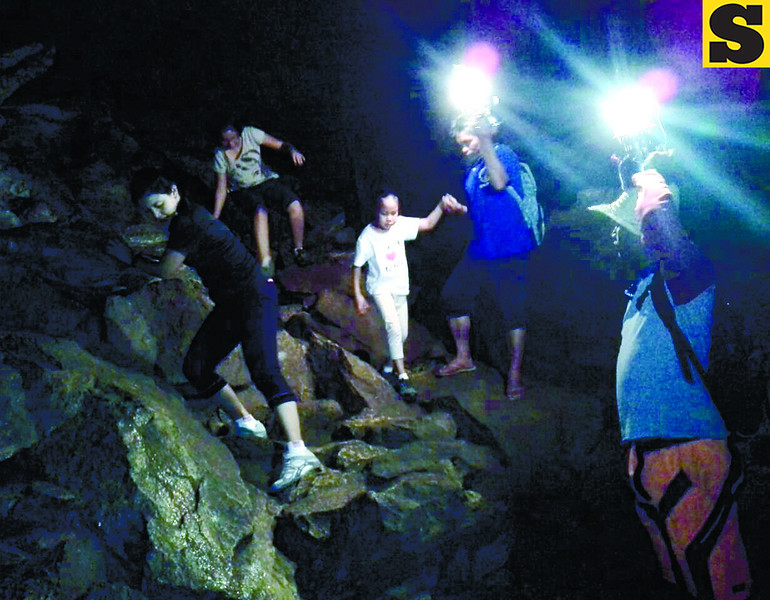 "Exploring the beautiful Sumaguing Cave is not as easy as it sounds, but not as hard as it looks. With the aid of local tour guides bearing ""petromax"" lamps, travelers of all ages can do a bit of spelunking in Sagada's biggest cave. (Noel S. Villaflor photo)"
