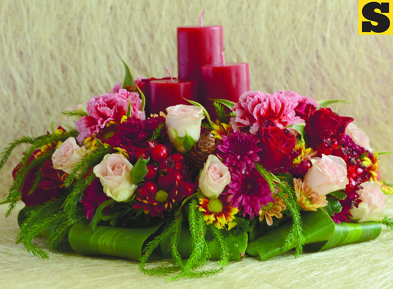 """Wreath-inspired traditional Christmas arrangement is made with candles, mixed fl owers (carnations, roses, mums) and pine needles for a """"Chrismassy"""" effect. The fl oral arrangement exudes a feeling of warmth to brighten up the Noche Buena table."""