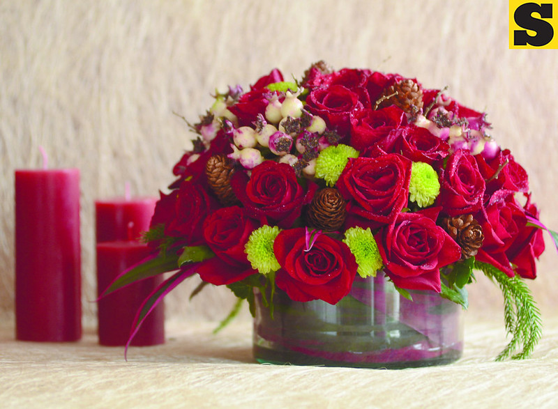 "Holland roses are accented with green ""buttons,"" berries and cones. Ideal for modern setting of small and intimate gatherings using small tables"