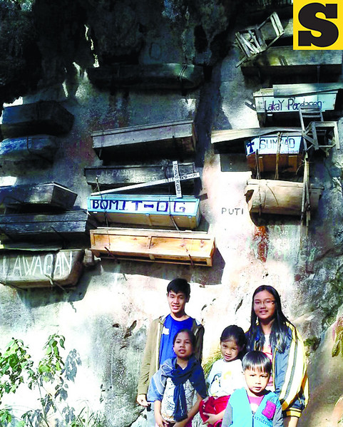 Hanging out under the Hanging Coffins are (from left) Angelo, Arwen, Angeli, Cyan and Amber. They walked through a cemetery and a pine tree forest, climbed down a steep slope all the way to the bottom of a valley, to get near the Hanging Coffins suspended from a karst cliff on the other side. (Noel S. Villaflor photo)