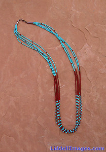 "(2)   Five strand turquoise and pipestone heishi necklace - 24""  Pipestone (Catlinite)..  the claystone (a mass of limestone found in a clay deposit) is soft and easily carved, due to its peculiar composition. Consequently, it is used by the American Indians to make the ceremonial pipes which are an integral part of their religious and civic ceremonies. Because of this specific use, the rock is commonly called ""pipestone.""  The literal meaning of Heishi is ""shell"" and specifically refers to pieces of shell, which have been drilled, and ground into beads and then strung into necklaces. More and more frequently, however, heishi (hee-shee) has come to refer to hand-made tiny beads made of any natural material. The origin of heishi is fascinating indeed, and is inescapably linked to the ancient history of the people most proficient in its making, the Santa Domingo Pueblo Indians. It is safe to say that this is the oldest form of jewelry in New Mexico (and perhaps in North American), pre-dating the introduction of metals. Centuries ago, the shells used by the Pueblo Indian to make beads were obtained in trade from the Gulf of California. It will take from 2 days to a week to prepare a single strand of heishi. A string of good heishi will have a uniform consistency. If you gently pull it through your hand, it should feel like a single serpent-like piece. (Note: Precisely because of the handwork involved, a fine string of heishi may contain a lightly flawed or chipped individual bead.) This information is from the Indian Arts & Crafts Association Collector's Guides to Albuquerque, Santa Fe and Taos."