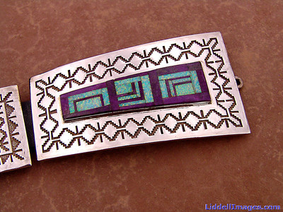 "(13) Belt buckle of the eleven piece sterling silver, opal and sugilite concho belt - 32"" by Navajo Harrison Jim.  Sugilite is a rich royal blue mineral widely enjoyed as an ornamental stone. Although massive sugilite samples are opaque, crystals are usually transparent to translucent. Sugilite is a member of the sugilite group and together with hauyne, nosean and lazurite is a common constituent of lapis lazuli."