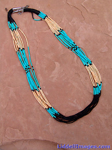 "(4) Ten strand turquoise melon shell and jet heishi necklace - 26""  The literal meaning of Heishi is ""shell"" and specifically refers to pieces of shell, which have been drilled, and ground into beads and then strung into necklaces. More and more frequently, however, heishi (hee-shee) has come to refer to hand-made tiny beads made of any natural material. The origin of heishi is fascinating indeed, and is inescapably linked to the ancient history of the people most proficient in its making, the Santa Domingo Pueblo Indians. It is safe to say that this is the oldest form of jewelry in New Mexico (and perhaps in North American), pre-dating the introduction of metals. Centuries ago, the shells used by the Pueblo Indian to make beads were obtained in trade from the Gulf of California. It will take from 2 days to a week to prepare a single strand of heishi. A string of good heishi will have a uniform consistency. If you gently pull it through your hand, it should feel like a single serpent-like piece. (Note: Precisely because of the handwork involved, a fine string of heishi may contain a lightly flawed or chipped individual bead.) This information is from the Indian Arts & Crafts Association and the Wingspread Communications publishers of the Collector's Guides to Albuquerque, Santa Fe and Taos."