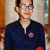 """Photo by Lily Ko<br /> <br /> In This Scene: Clen, of Hyphen magazine, in a tiny polka-dot printed shirt, self-made cloth button and glasses, """"from a warehouse in Beijing."""" He said he paid $15 for the frames, with prescription lenses--wow. I really love the matte black frames."""